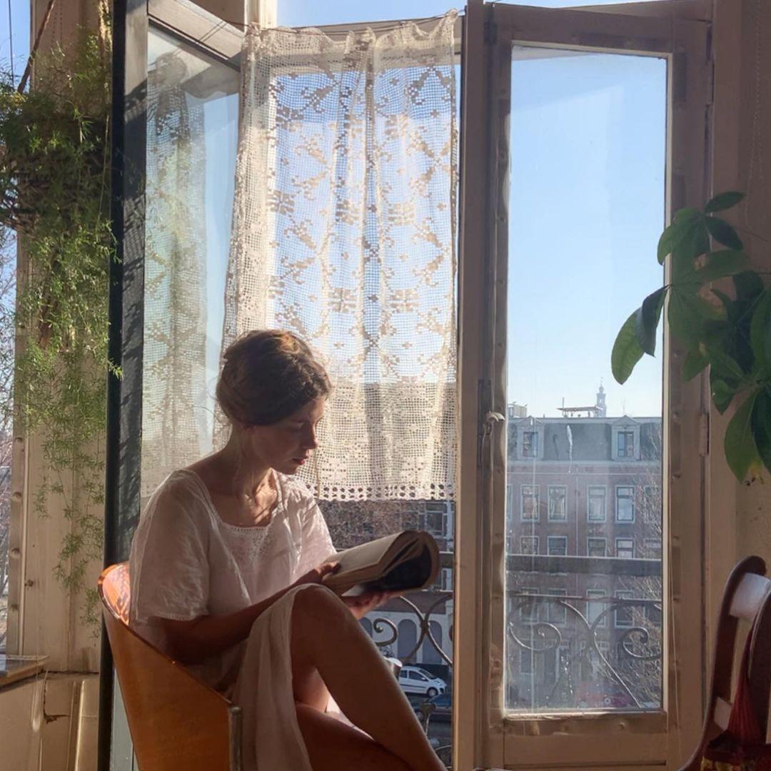 Moça lendo livro e tomando sol na janela